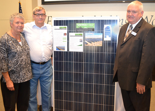 On the left, Linda and Gail Palmberg stand next to a solar panel in the community solar array they had won, as Keith Miller, Chairman of Midwest Energy Board of Directors, is on the far right side of the photo.