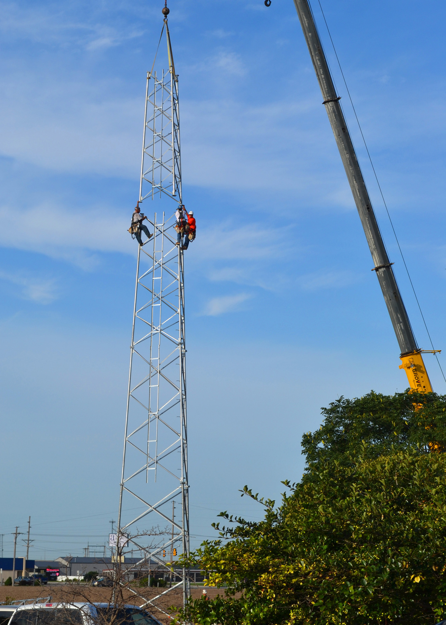 Three contractors climb the base of what will be a 150-foot tall steel communications tower at Midwest Energy's office in Hays.  The tower is one of nearly 60 system-wide to support new automated meters and other communications needs.
