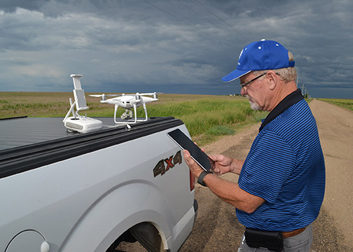 A man in a blue shirt stands at the bed of a pickup truck, on which a white drone sits.  The man is holding the drone's remote control, and is syncing it with the drone.