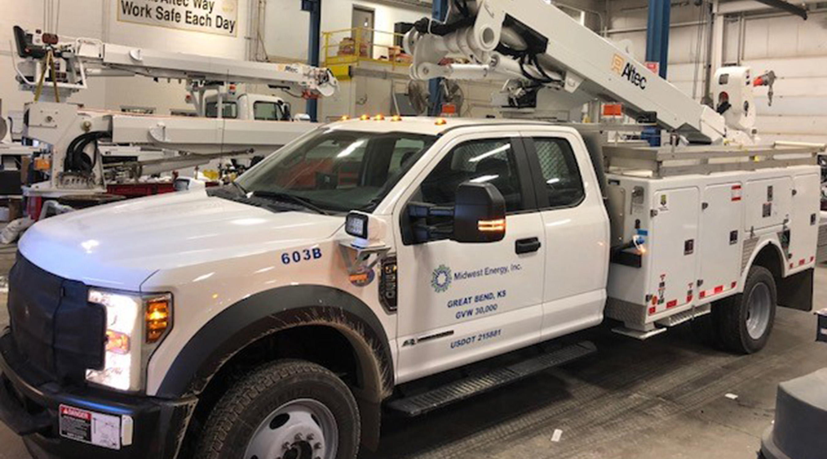 A photo of a Midwest Energy service bucket truck inside of a garage.