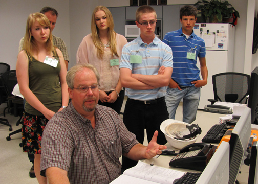 Mike Prindle, Plant Manger of Midwest Energy's Goodman Energy Center, demonstrates the plant's operating console to students selected to represent Midwest Energy during a week-long