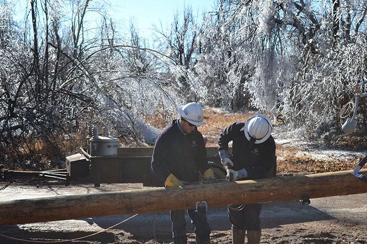 Midwest Energy linemen from Hays build a new pole to replace one that broke near Garfield, Kan.  The trees in the background show evidence of the nearly two inches of ice deposited on them by Ice Storm Jupiter.