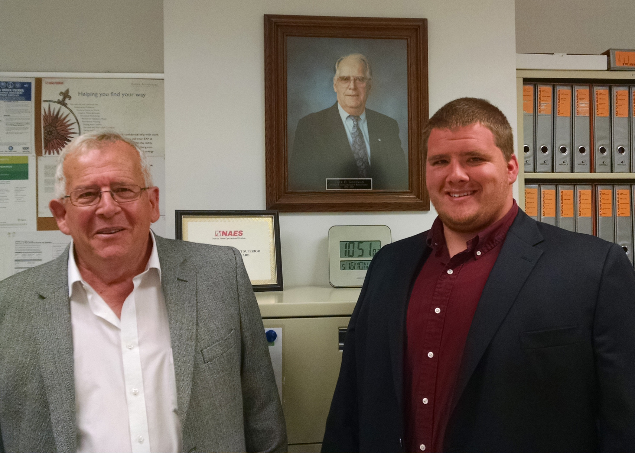 Marc Goodman and his son, Daniel Goodman, stand in front of a portrait of Jack Goodman, former president and general manager at Midwest Energy and for whom the Goodman Energy Center is named.  Jack Goodman is Marc's father and Daniel's grandfather.