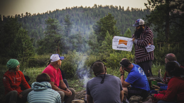 A group of veterans participating in the No Barriers Warriors program sit and talk around a campfire in the mountains near Red Feather Lakes, Colorado.