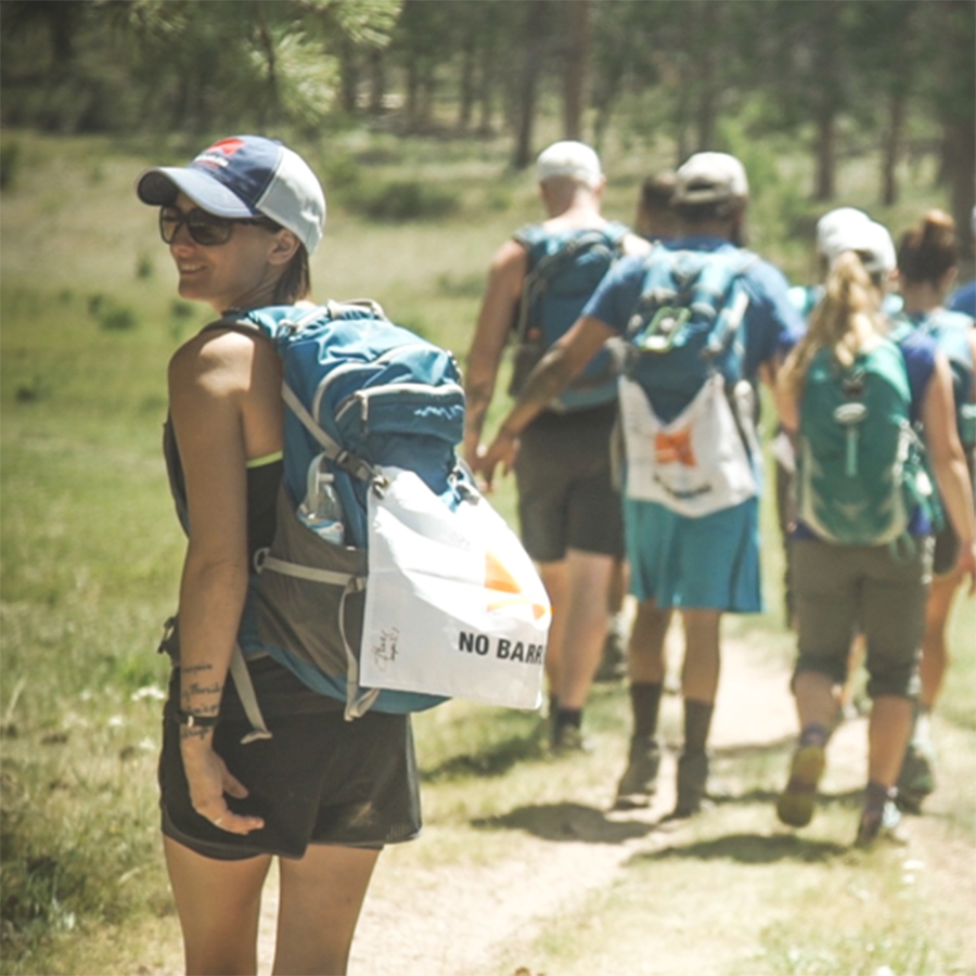 A group of veterans participating in the No Barriers Warriors program hike in the mountains near Red Feather Lakes, Colorado. A female participant is turning to face the camera as others walk ahead.