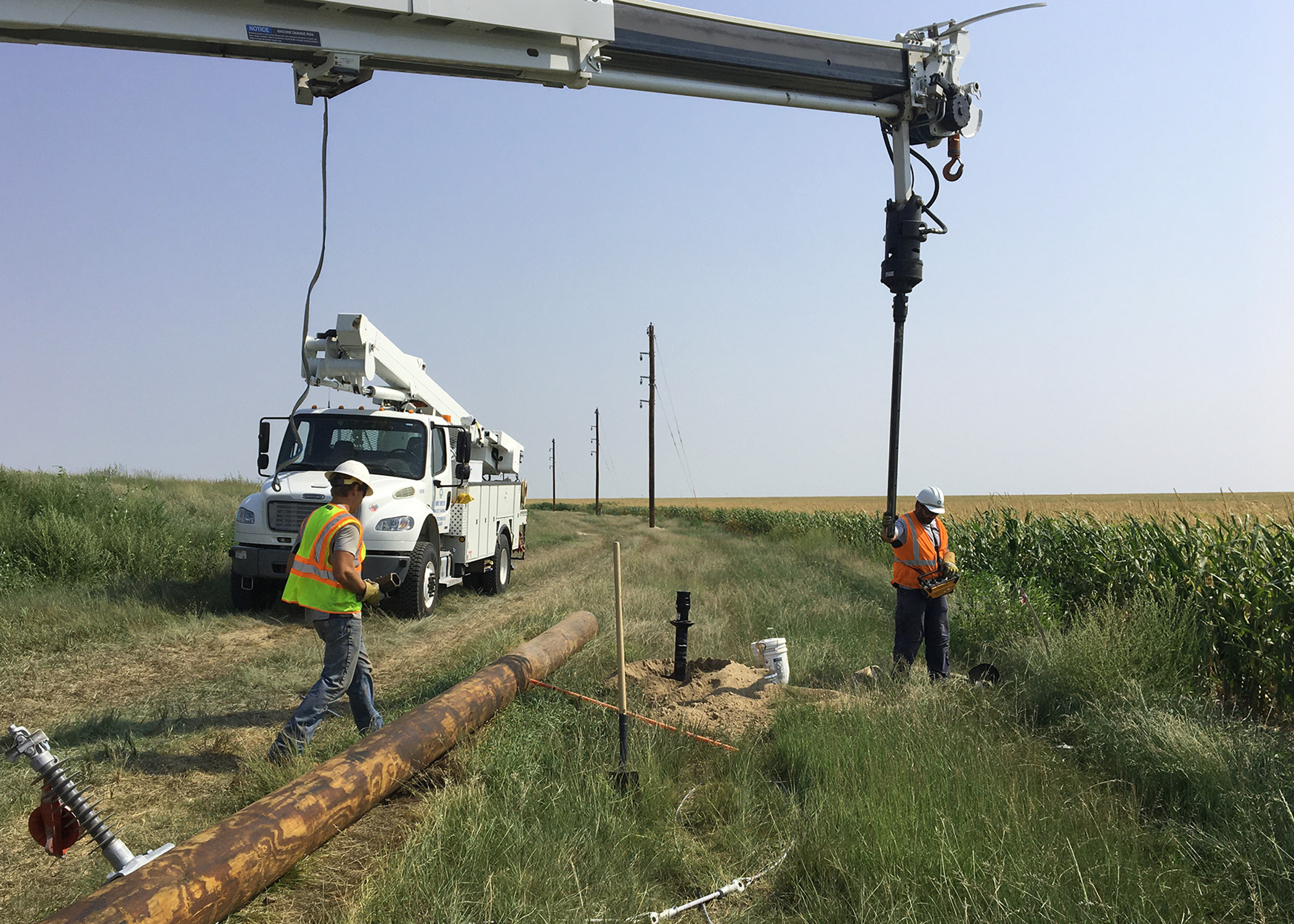 Two linemen in safety vests, working in a ditch near US-40, use a truck boom-mounted auger to drill a hole for a new power pole west of Winona, Kansas.