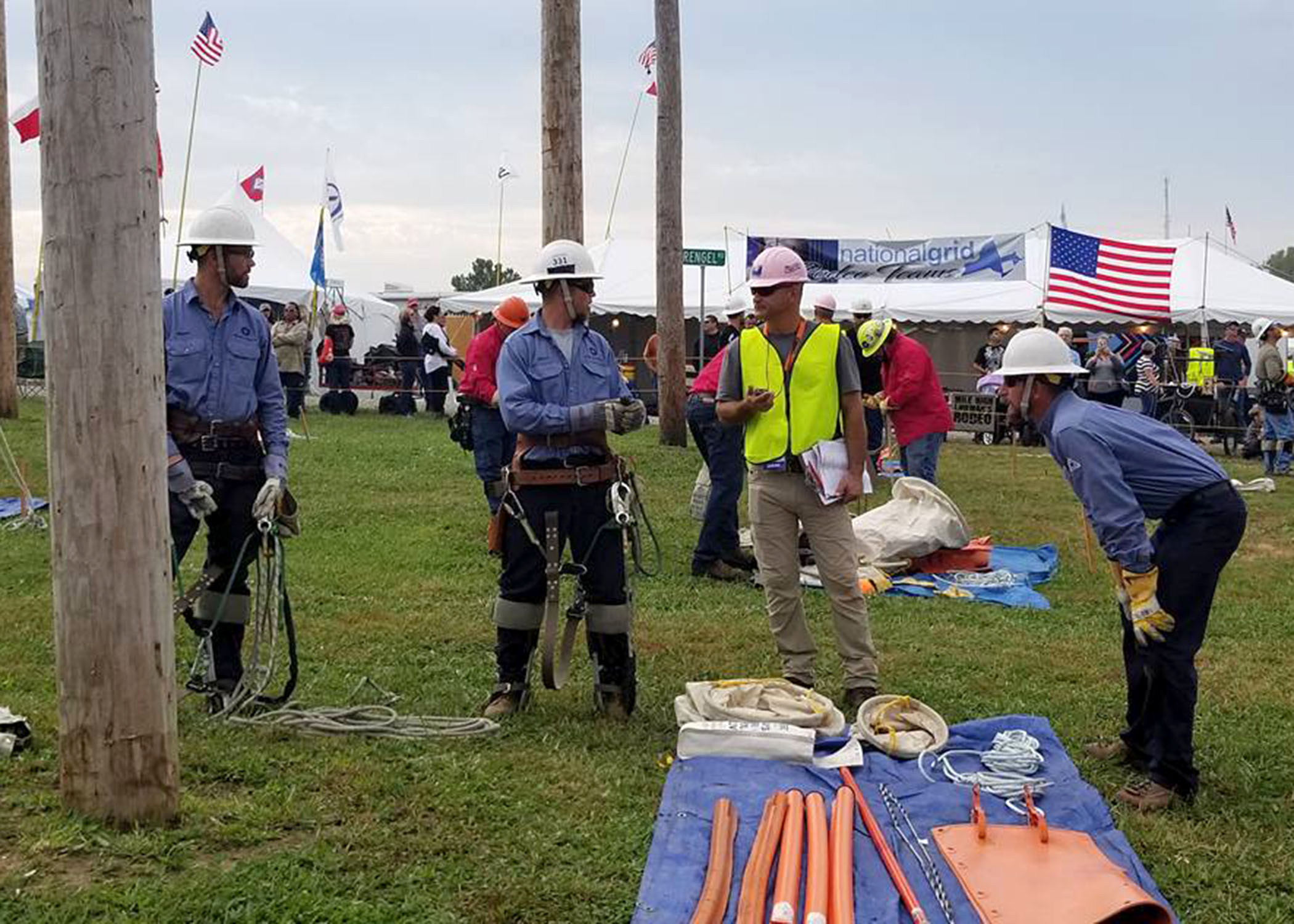 A photo of Midwest Energy's Hays Journeyman team, of Shawn Slaubaugh, Butch Hamel and Brian Legleiter, discusses an upcoming event with a judge at the International Lineman's Rodeo in Bonner Springs, Oct. 14.