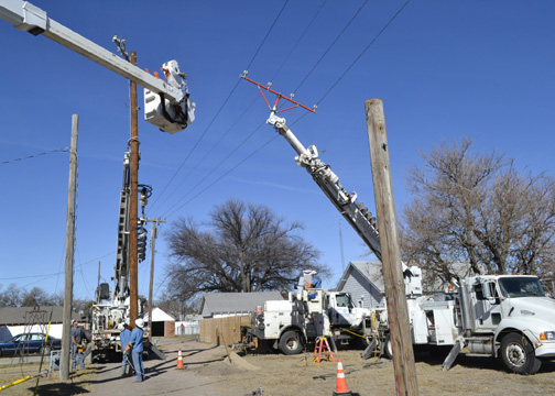 Midwest Energy line crews from Oakley, Colby and Sharon Springs combine to replace poles behind a church at Center and 4th in Oakley. Since 2006, Midwest Energy has replaced more than 800 poles and 300 transformers to improve reliability for customers in the city.