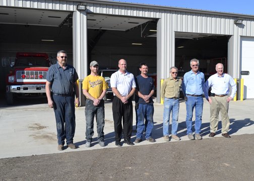 Representatives from the Quinter Volunteer Fire Department, QMC Construction and Midwest Energy pose in front of the department's new station in Nov. 2012.