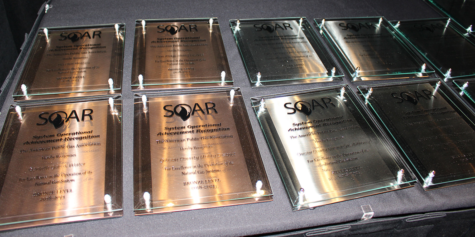 A photo of several award plaques laid on a table; Midwest Energy was one of just 18 natural gas utilities nationwide to receive the APGA's prestigious SOAR award for 2018.