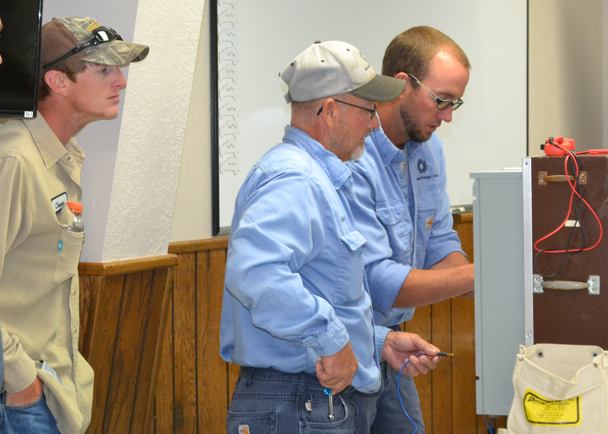 A picture of three linemen, one wearing a tan shirt and two wearing blue shirts, conducting a test on a meter can simulator during metering school.