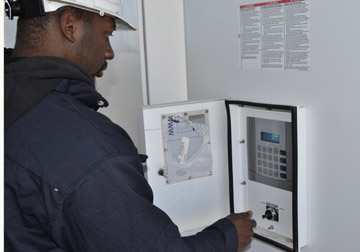 A technician from Schneider Electric turns a switch on an inverter, making the Community Solar Array