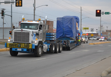 A natural gas generator, weighing 150 tons, is moved from the Hays Rail Yard up Vine St. in Hays on a special 130-foot trailer pulled by a white semi-truck. The generator is covered with a blue tarp.