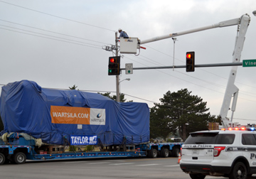 A natural gas generator, weighing 150 tons, is transported on Vine St. in Hays on a specialized trailer pulled by a white semi-truck. The generator is covered with a blue tarp. A Midwest Energy lineman, working from a bucket lift utility truck, raises a traffic signal to allow the generator to pass safely. A Hays Police Department SUV is in the lower right corner providing traffic control as the generator crosses the intersection.