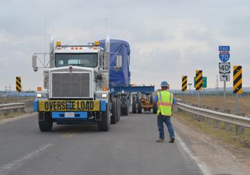 A natural gas generator, weighing 150 tons, is transported over I-70 via Bypass 183 just northwest of Hays. A white semi-truck pulls the massive generator with 130-foot specialized trailer. The trailer is mounted with several outriggers to displace the weight of the generator. Each outrigger can displace 20-tons of weight. The generator is covered with a blue tarp.