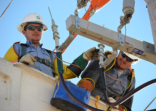A photo of Midwest Energy linemen Weston Riffel from Colby, and Brandon Salmans of Hoxie, make final connections before energizing a section of line.
