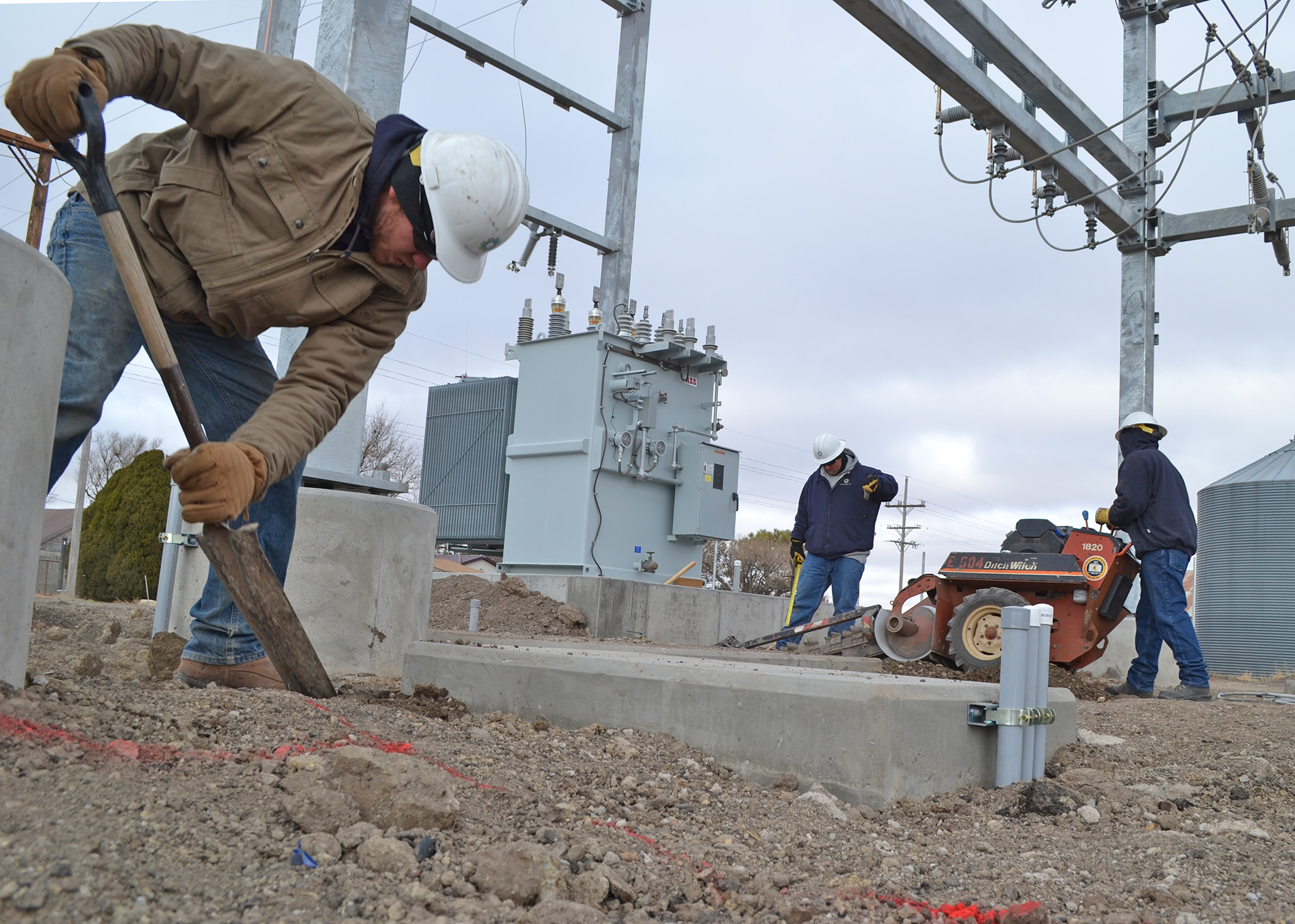 A photo of Midwest Energy linemen shoveling a trench, and operating a trenching machine, inside a new substation in Winona, Kansas.