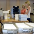 Sharon and Nikki, Midwest Energy Finance Department employees in Hays, prepare 13,675 capital credit checks for mailing to former Midwest Energy members. Credits paid out this year were earned in 1990-1991, and many members have changed addresses since then.