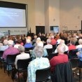 More than 120 Midwest Energy members sit in chairs as they view a PowerPoint presentation displayed on a wall to the left.  The 2015 Annual meeting was held in the Robbins Center on the Fort Hays State University Campus in Hays, Kan.