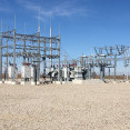 A photo of an electrical substation with steel structures and multiple transformers.