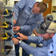 A picture of two Midwest Energy linemen in blue shirts work on a metering can simulator.