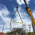 A very large crane from Hess Services is rigged with yellow harnesses to hoist a skid-mounted substation onto a concrete pad.