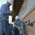 Two natural gas workers in blue shirts and white helmets attach a gas meter to the exterior of a brick home.