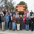 More than two dozen citizens of Natoma, Kansas stand in front of a large outdoor LED sign installed in the city to keep members informed of community events.