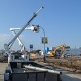 An image of a construction zone, with an electric crew truck lifting a streetlight off of its base; in the foreground are removed streetlights in a trailer, awaiting removal.