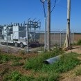 An image of a mobile electric substation, parked within a chain-link fence enclosure next to two power poles; a lineman in a blue shirt stands in a roadway and looks inward at the setup.