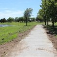 A new pedestrian and bicycle trail was partially paid for by a Midwest Energy grant. The photo shows the new concrete path with trees on the right side.  A slope to the left of the walkway leads to a lake.