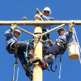 A photo of three linemen in blue shirts, manually climbing to the top of a training power pole, and looking down waving from atop the crossarm.