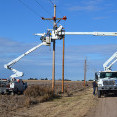 A photo of two bucket trucks, with booms extended, as linemen work on overhead power lines.