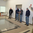 Five men look at a zero-entry physical therapy pool at the Rooks County Health Center in Plainville, Kansas, while one man explains its operation.