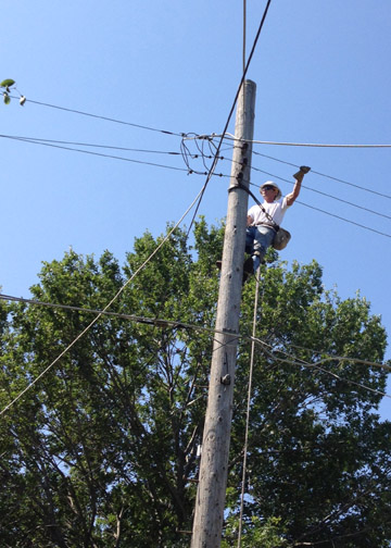Shane Wente, Acting Line Foreman at Colby, climbs a pole to make repairs to wires in Wichita.