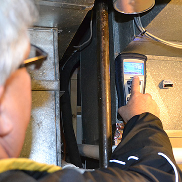 A Midwest Energy auditor checks a home's HVAC air system as part of a whole-home energy audit.