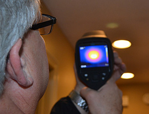 A Midwest Energy auditor uses an infrared camera to measure energy loss around ceiling lights during a whole-home energy audit.