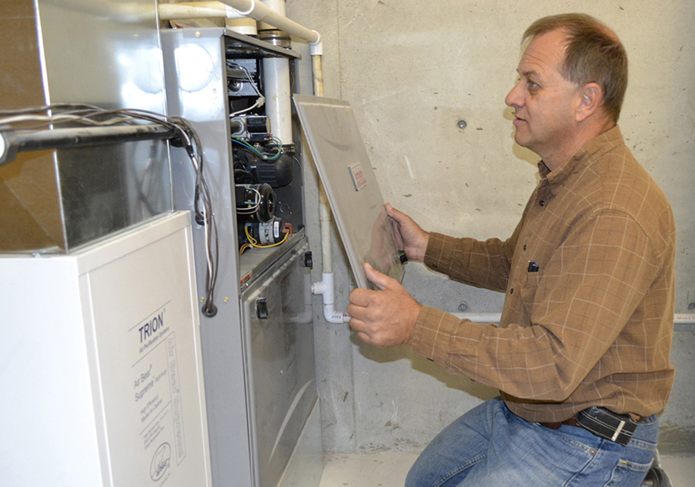 A Midwest Energy auditor inspects a newly-installed HVAC unit, for a customer participating in the Howsmart program.