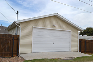 Picture of a detached two-car garage with yellow siding, behind a home.