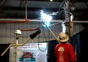 A Midwest Energy lineman utilizes a special high-voltage safety trailer demonstration at the Kansas State Fair in Hutchinson. During the demonstration, a pineapple is electrified to show the hazards of touching a live powerline.